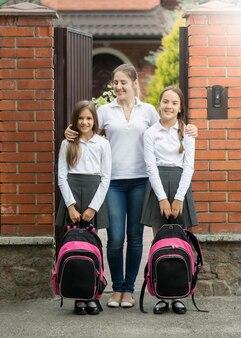 Madre sorridente in piedi sulla soglia con due figlie in partenza per la scuola