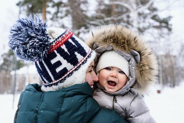 Madre sorridente in giacca verde invernale e cappello con pompon che abbraccia il suo bambino nel parco in inverno, concetto di maternità felice