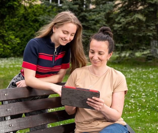 Madre sorridente con sua figlia utilizzando la tavoletta digitale e riposando nel parco