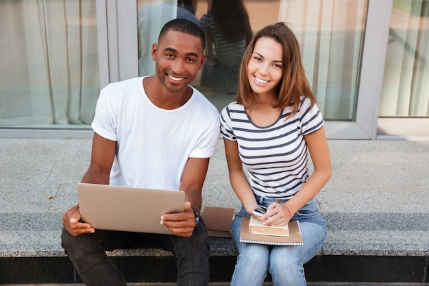 Giovani coppie multietniche sorridenti che utilizzano insieme il computer portatile all'aperto