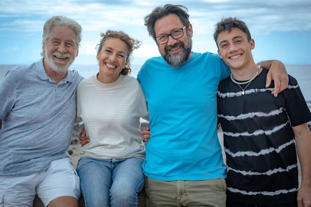 Sorridente famiglia multigenerazionale, seduti all'aperto in riva al mare. da adulto anziano a ragazzo adolescente