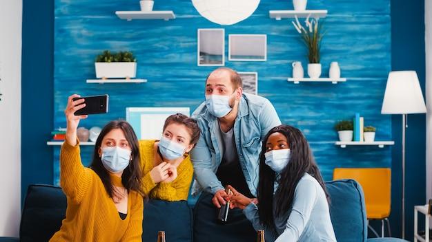 Amici multirazziali sorridenti seduti sul divano con maschere di protezione, facendo selfie su smartphone