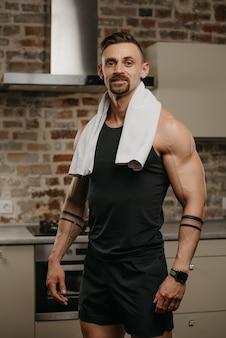 Un uomo muscoloso sorridente con un asciugamano bianco sulle spalle posa dopo un allenamento nel suo appartamento
