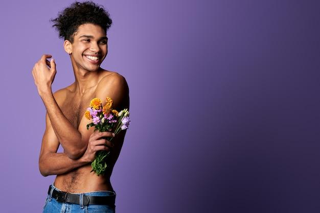 Sorridente modello transgender muscoloso con bouquet ritratto torso nudo giovane uomo di genere trans