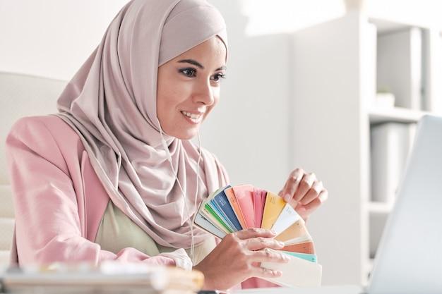 Sorridente designer musulmano in hijab rosa che mostra il campione di colore al cliente mentre gli parla tramite un'app di videoconferenza