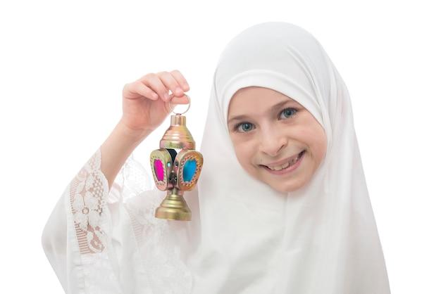 Sorridente ragazzina musulmana in hijab che tiene la lanterna del ramadan