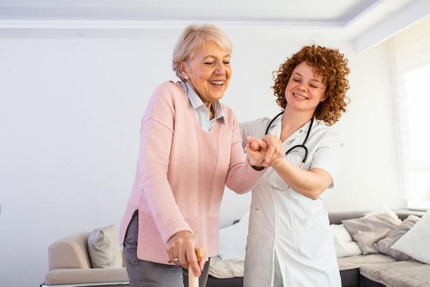 Infermiera sorridente che aiuta signora maggiore a camminare intorno alla casa di cura