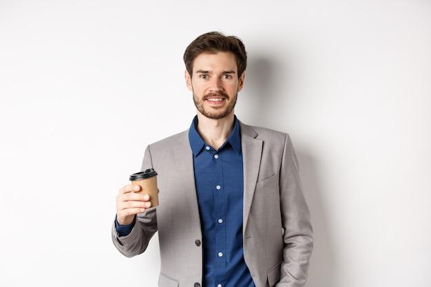 Sorridente impiegato in tuta bere caffè dal bicchiere di carta, avendo pausa dopo il lavoro al bar, in piedi su sfondo bianco.