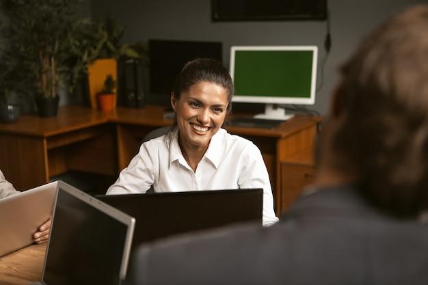 Sorridente impiegato, giovane donna in camicia bianca al colloquio.
