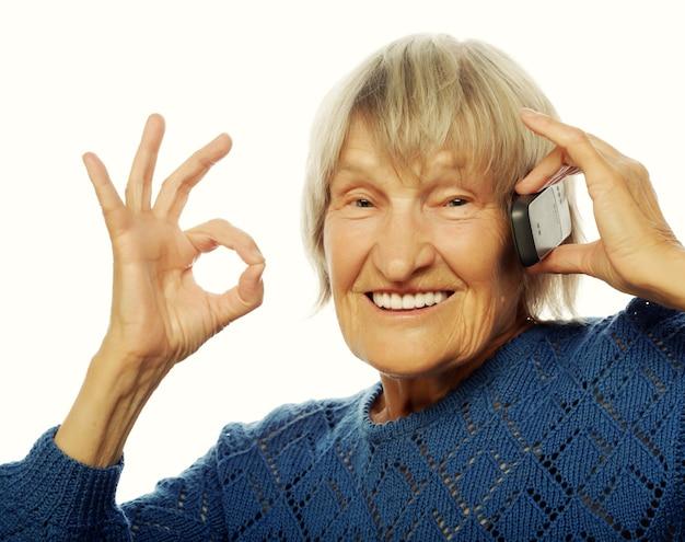 Signora anziana sorridente che comunica tramite telefono cellulare