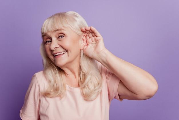 La donna anziana sorridente con la mano sull'orecchio ascolta i suoni isolati su fondo viola