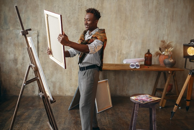 Pittore sorridente con tela in piedi vicino al cavalletto. l'artista maschio disegna sul posto di lavoro, il maestro creativo lavora in officina