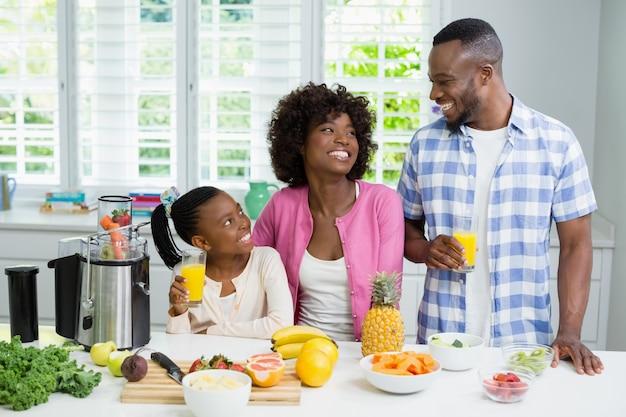 Genitori e figlia sorridenti che mangiano un bicchiere di succo d'arancia in cucina a casa