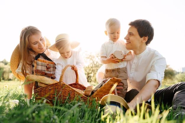 Genitori sorridenti aiutano i bambini piccoli figlio e figlia a smontare il cesto di vimini su un prato verde nel parco in