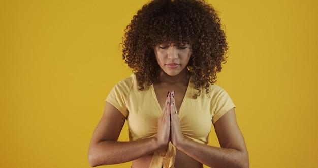 Sorridente giovane donna pacifica che pratica yoga e meditazione. donna calma che fa il gesto di namaste e che guarda l'obbiettivo. concetto di yoga. gratitudine.