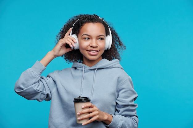 Sorridente ragazza adolescente nera pensierosa ascoltando musica in cuffie wireless e bere caffè su sfondo blu
