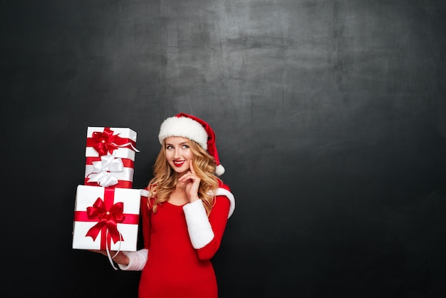Sorridente giovane donna pensierosa in cappello di babbo natale che tiene scatole regalo
