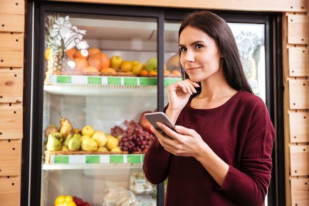 Sorridente giovane donna pensierosa che utilizza il telefono cellulare e pensa in un negozio di alimentari