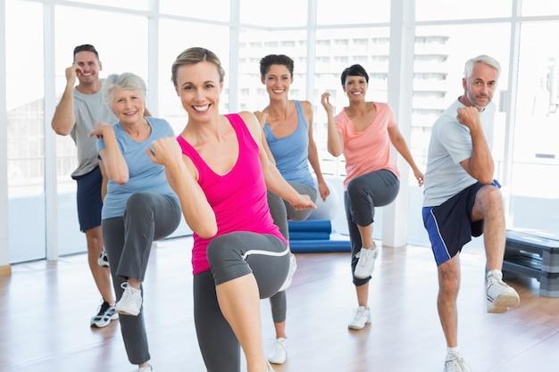 La gente sorridente che fa l'esercizio di forma fisica di potere alla classe di yoga