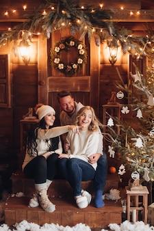 Gente sorridente che si siede sulla veranda in legno davanti alla porta con la corona di natale