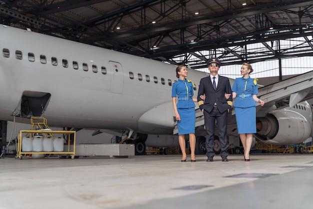 Pilota sorridente e assistenti di volo che camminano insieme nell'hangar