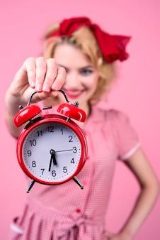 Sorridente donna pinup con orologio incredibile donna pin up in abito rosso tiene orologio rosso stile pin up