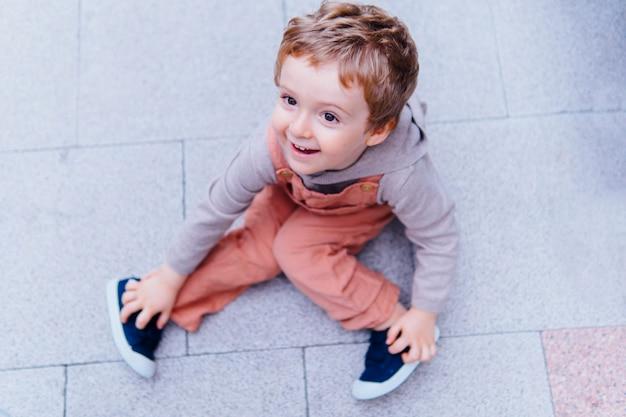 Sorridente bambino giocoso di tre anni seduto per terra in strada