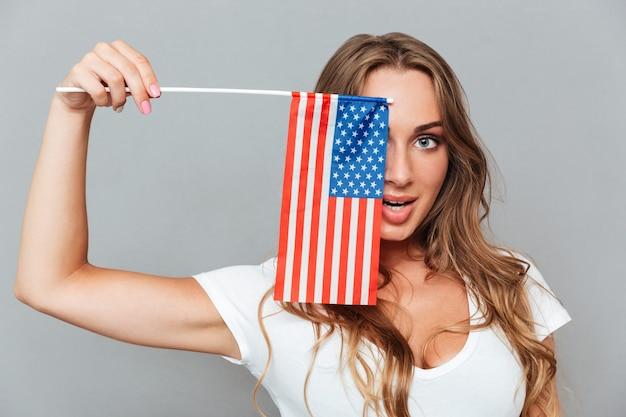 La giovane donna allegra sorridente si coprì l'occhio con la bandiera dell'america sul muro grigio