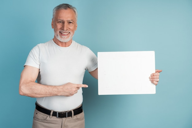 Sorridente, piacevole, uomo anziano tiene un pezzo di carta bianco e lo indica.