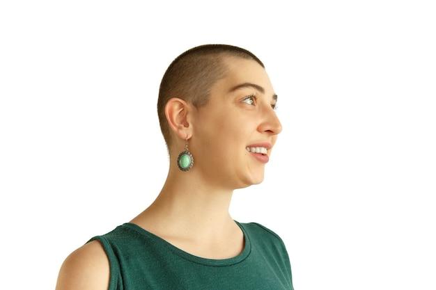 Sorridente. ritratto di giovane donna caucasica con aspetto strano sul muro bianco. look insolito con tatuaggi e calvo. emozioni umane, espressione facciale, vendite, concetto di annuncio. cultura giovanile.