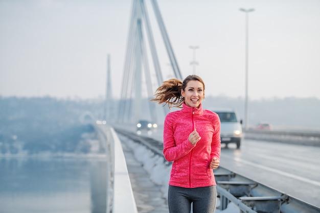 Brunette caucasico positivo sorridente in abiti sportivi e con la coda di cavallo che funziona sul ponticello. orario invernale. fitness all'aperto.