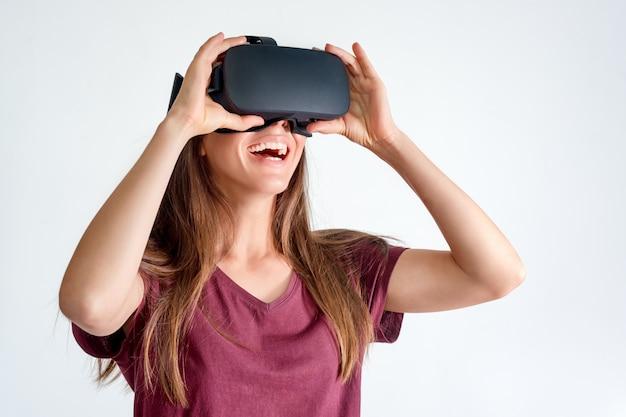 Cuffia avricolare d'uso sorridente degli occhiali di protezione di realtà virtuale della donna positiva, scatola del vr. connessione, tecnologia, nuova generazione, concetto di progresso. ragazza che prova a toccare gli oggetti nella realtà virtuale. studio girato su grigio