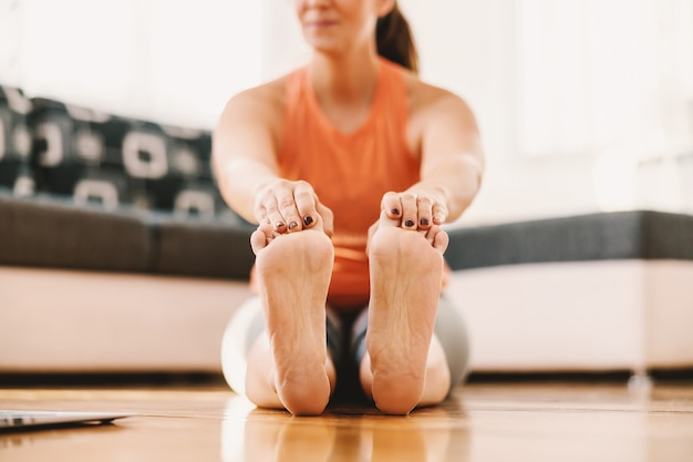 Sorridente sportiva incinta seduta sul pavimento a casa