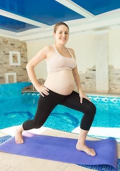 Sorridente donna incinta che fa yoga in palestra accanto alla piscina