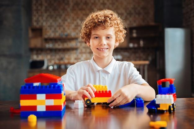 Sorridente ragazzo preadolescenziale in una camicia bianca seduto a un tavolo di legno con un giocattolo auto costruito nelle sue mani ed esamina la macchina fotografica con gli occhi pieni di felicità.