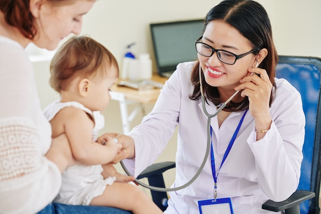 Medico abbastanza asiatico sorridente che ascolta il respiro della piccola neonata che si siede sui giri della madre