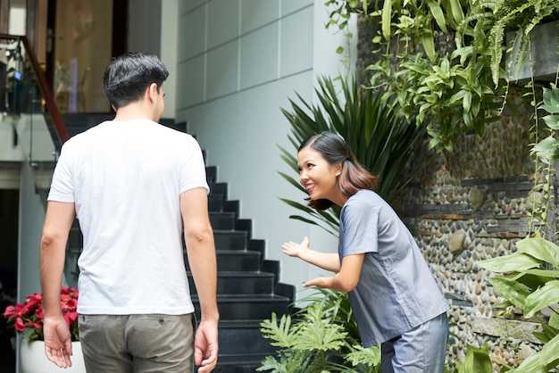Sorridente bella donna asiatica che si inchina all'uomo che entra nell'edificio del salone spa e fa un gesto invitante