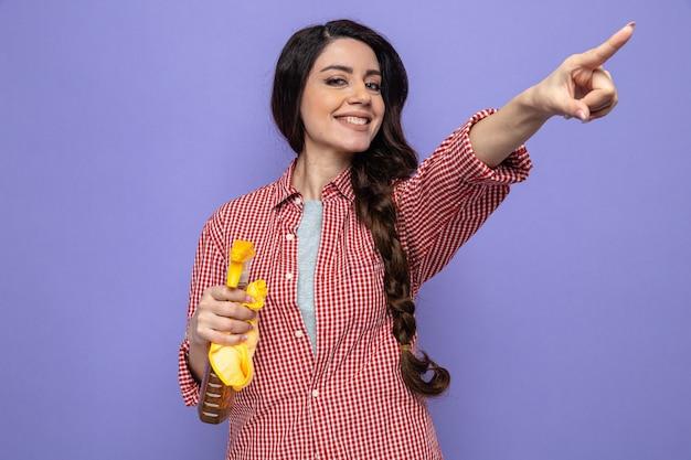 Sorridente donna abbastanza caucasica più pulita che tiene in mano panni per la pulizia e detergente spray e punta a lato