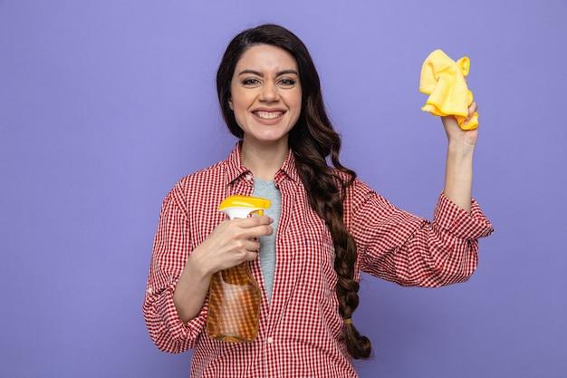Sorridente donna delle pulizie piuttosto caucasica che tiene in mano panni per la pulizia e detergente spray
