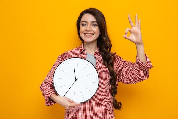 Sorridente donna abbastanza caucasica più pulita che tiene l'orologio e fa un gesto ok con le dita Foto Premium