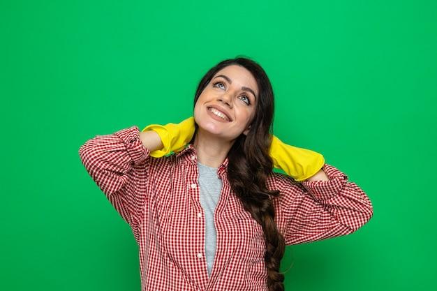 Sorridente donna delle pulizie piuttosto caucasica con guanti di gomma che si tiene il collo dietro e guarda in alto