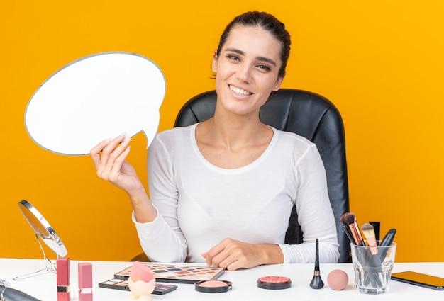 Sorridente bella donna caucasica seduta al tavolo con strumenti per il trucco che tiene il fumetto isolato sulla parete arancione con spazio di copia