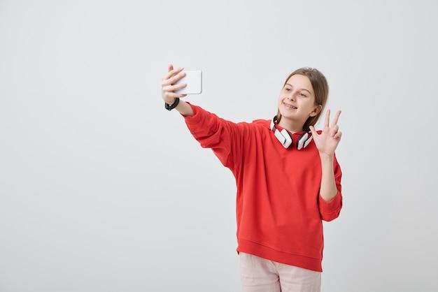 Sorridente bella ragazza in felpa con cappuccio rossa che mostra tre dita durante l'assunzione di selfie sullo smartphone