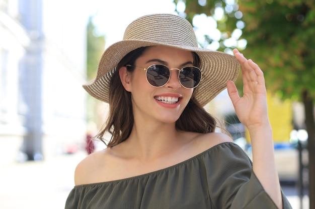 Sorridente bella ragazza che indossa occhiali da sole e cappello estivo e guarda la macchina fotografica mentre si cammina in una strada cittadina.