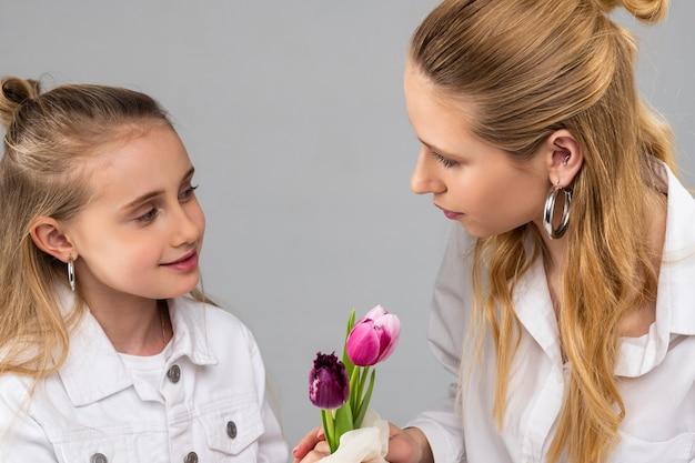 Bella ragazza sorridente in giacca bianca che regala fiori a sua sorella dai capelli chiari mentre è carina