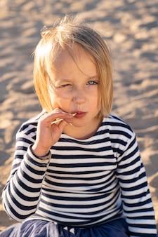Sorridente bambina graziosa con gli occhi azzurri in maglietta a righe che guarda l'obbiettivo, succhiare lecca-lecca, strabismo dal sole all'aperto.