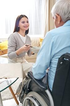 Infermiera graziosa sorridente che alimenta uomo disabile anziano in sedia a rotelle e parla con lui nel soggiorno