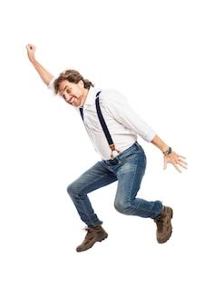 Un uomo sorridente piuttosto rossa con la barba in jeans e una camicia bianca sta saltando. isolato sul muro bianco. verticale.