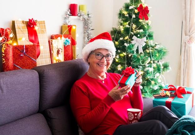 Una donna piuttosto anziana sorridente con gli occhiali e il cappello di babbo natale che guarda l'obbiettivo felicemente con una confezione regalo ricevuta per natale. seduti a casa con luci e addobbi