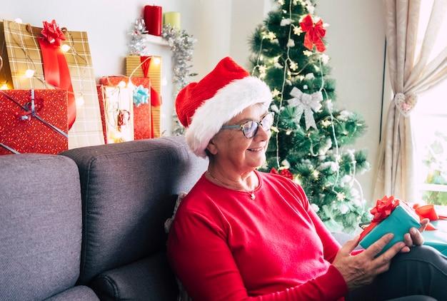 Una donna piuttosto anziana sorridente con gli occhiali e il cappello di babbo natale che guarda la confezione regalo ricevuta per natale. seduti a casa con luci e addobbi